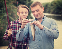 Cheerful man with son looking at fish on hook Stock Images