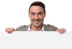 Cheerful man standing behind a blank billboard Stock Photo