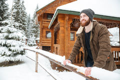 Cheerful man standing in front of wooden cottage at winter. Portrait of cheerful handsome bearded man standing in front of wooden cottage in winter forest Royalty Free Stock Photos