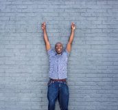 Cheerful man standing with his hands raised against a gray wall Stock Photography