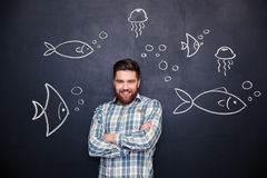 Cheerful man standing over blackboard with drawn fishes and jellyfishes Royalty Free Stock Photo