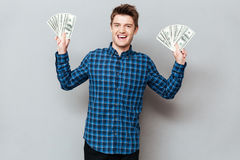 Cheerful man standing over grey wall holding money. Image of young cheerful man standing over grey wall and looking at camera while holding money royalty free stock photography