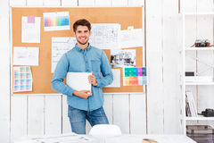 Cheerful man standing at the task board and holding laptop Royalty Free Stock Photos