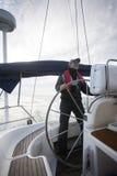 Cheerful Man Steering Wheel Of Yacht During Sunset stock photo