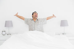 Cheerful man stretching his arms in bed Stock Photo