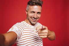 Cheerful man in striped t-shirt smiling and pointing finger at y stock photography