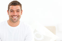 Cheerful man stting on his bed at home Stock Images