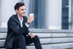Cheerful man in suit is relaxing with hot drink Royalty Free Stock Image