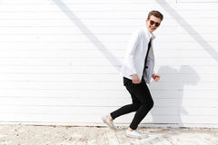 Cheerful man in sunglasses running over white wall background Stock Photos