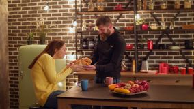 Cheerful man surprising girlfriend with croissants. Positive handsome bearded man surprising his joyful girlfriend with fresh baked croissants in domestic stock footage