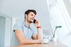 Cheerful man talking on cell phone while having coffee break Royalty Free Stock Photography