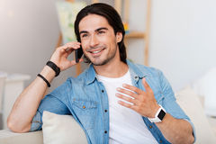Cheerful man talking on cell phone. Nice talk. Cheerful smiling bearded man sitting on the couch and expressing joy while talking on cell phone stock photo