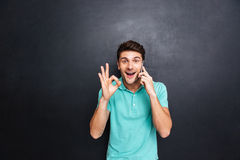 Cheerful man talking on cell phone and showing ok sign Stock Photo