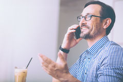 Cheerful man talking on phone in the cafe Stock Photo