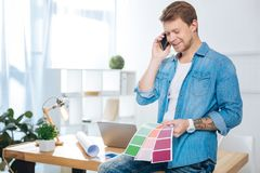 Cheerful man talking on the phone while holding color palettes. Phone talk. Friendly young cheerful designer looking glad while talking on the phone and sitting stock image