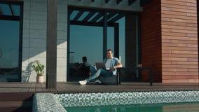 Cheerful man talking on skype conversation outside on luxury house stock footage