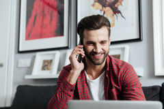 Cheerful man talking by telephone. Picture of young cheerful man sitting at home indoors while using laptop computer talking by telephone. Looking aside Royalty Free Stock Photography