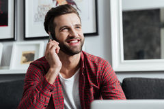 Cheerful man talking by telephone. Picture of young cheerful man sitting at home indoors while using laptop computer talking by telephone. Looking aside Royalty Free Stock Photos