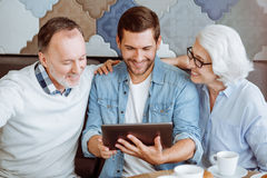 Cheerful man and their grandparent sitting in the cafe. In the metwork. Positive delighted senior couple and their grandson sitting in the cafe and using tablet Stock Images