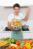 Cheerful man tossing vegetables in kitchen Royalty Free Stock Photography