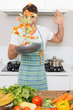Cheerful man tossing vegetables in kitchen Royalty Free Stock Photos