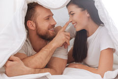 Cheerful man touching his wife nose. Got your nose. Adorable young couple lying underneath the blanket and having a pillow talk while a men touching his wife Royalty Free Stock Photo