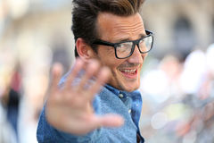 Cheerful man in town with eyeglasses. Cheerful guy with eyeglasses shwoing thumbs up Royalty Free Stock Image