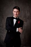 Cheerful man in tuxedo on grey background Royalty Free Stock Photos