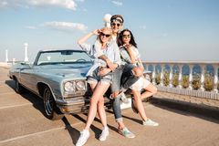 Cheerful man and two happy women standing near vintage cabriolet Stock Image