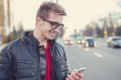 Cheerful man using cellphone outdoors royalty free stock photos