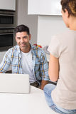 Cheerful man using laptop while partner sits on counter Stock Photo