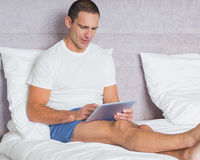 Cheerful man using tablet pc on bed Royalty Free Stock Photography