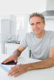 Cheerful man using tablet pc in kitchen Royalty Free Stock Image