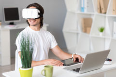 Cheerful man using virtual reality glasses. Charged with gladness. Positive content man wearing virtual reality glasses and using tablet while sitting at the stock photography