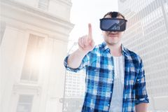 Cheerful man in VR headset his finger to press button Stock Photography
