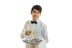 Cheerful man waiter in uniform and bowtie with glasses of white wine on silver tray smiling. In studio royalty free stock photography