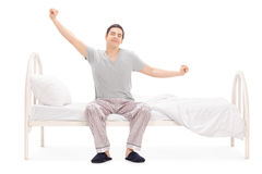 Cheerful man waking up from sleep and stretching. Seated on his bed isolated on white background Stock Images