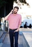 Cheerful man walking on sidewalk and talking on mobile phone Royalty Free Stock Images