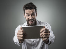 Cheerful man watching videos on tablet Stock Photography