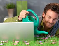 Cheerful man watering spring field table Stock Photography