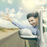 Cheerful man waving hand in the car Stock Image
