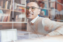 Cheerful man wearing eyeglasses while sitting in cafe. Photo of young cheerful man wearing eyeglasses while sitting in cafe and looking aside Royalty Free Stock Images