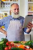 Cheerful man wearing gray apron using tablet to find a recipe Stock Photos