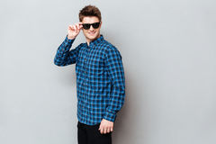 Cheerful man wearing sunglasses standing over grey wall. Photo of young cheerful man wearing sunglasses standing over grey wall and looking aside royalty free stock photo
