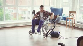 Cheerful man in a wheelchair is cleaning vacuuming. In home stock video