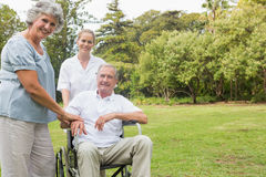 Cheerful man in a wheelchair with his nurse and wife Stock Image