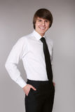 Cheerful man in white shirt with black tie keeping hands in pock Stock Photography