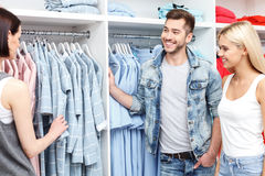 Cheerful man and woman choosing clothes in shop Stock Images