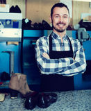 Cheerful man worker displaying his workplace. And tools in shoe repair workshop Royalty Free Stock Photos