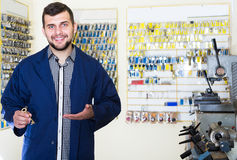 Cheerful man worker displaying result of his key making in works. Cheerful man worker displaying result of his key making at his workplace in workshop Royalty Free Stock Photo